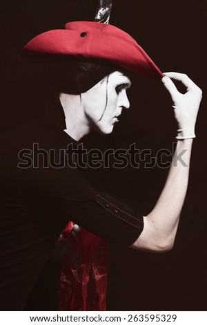Mime in a red cowboy hat on a black background - stock photo