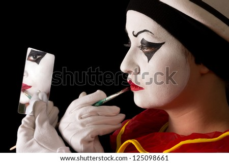 Mime performer applying Pierrot face paint with a brush - stock photo