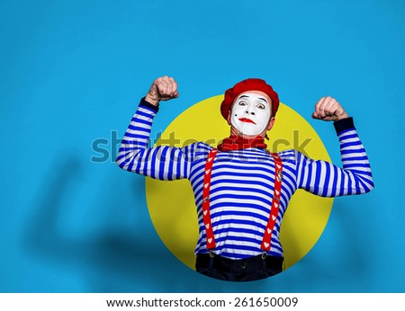 mime shows muscles on color background - stock photo