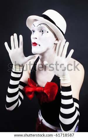 Mime with red bow ina white hat and striped gloves on  black background - stock photo