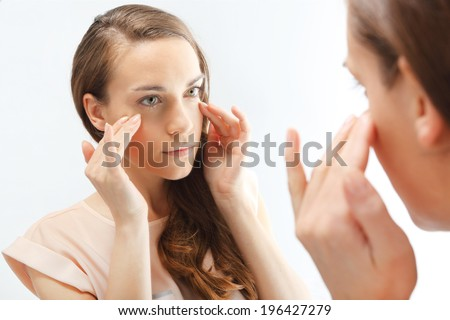 Mimic wrinkles ,signs of skin aging. First wrinkles .Portrait of a peer-reviewed in the mirror.  - stock photo
