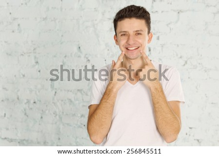 Mimicry of his face shows what he is going through. Show gesture with his hands. Show two fingers on his teeth. Indicate that the teeth are healthy and do not decay. Dental advertising. Emotional man  - stock photo