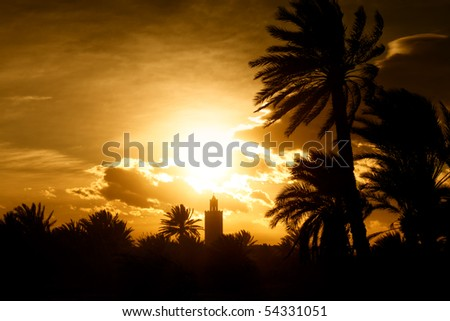 Minaret of a mosque at sunset with moody orange sky and dark palms. Concept of islam, prayer, religion and faith. - stock photo