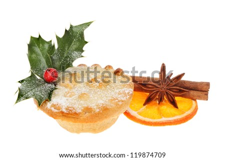 Mince pie decorated with holly and icing sugar with a slice of dried orange cinnamon and star anise - stock photo