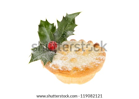 Mince pie dusted with icing sugar and decorated with a sprig of real holly isolated against white
