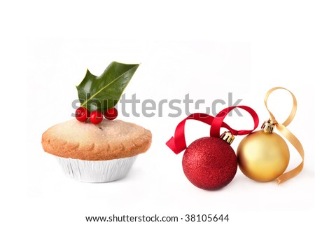 Mince pie with holly leaves and red berries, with two gold and red sparkling baubles with ribbons, over white background. - stock photo