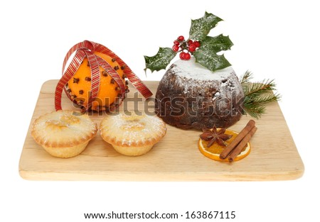 Mince pies, decorated orange and a Christmas pudding on a wooden board isolated against white
