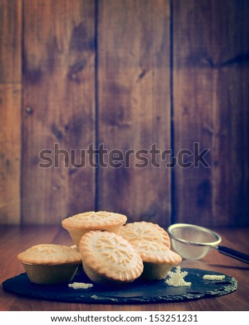 Mince pies on slate serving plate in rustic vintage setting - stock photo