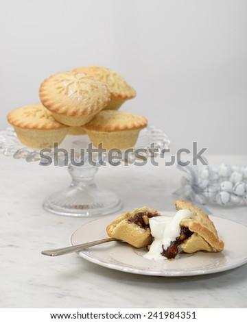 Mince pies with cream on plate with pastry fork - stock photo