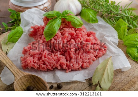 Minced beef raw on wood table with herbs and spice - stock photo