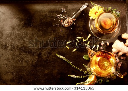 Minced Indian tea concept on black metal plate with copy space. Tasty ginger and rock sugar tea with flowers and peppermint with tea pot and tea cup - stock photo