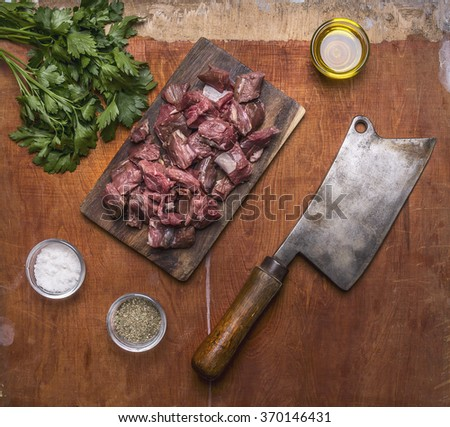 Minced lamb on a cutting board with a meat cleaver, herbs and spices on wooden rustic background top view close up - stock photo