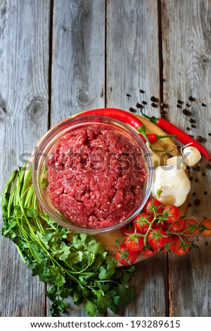 Minced meat, chili pepper, cherry tomato, cilantro and garlic - traditional ingredients of Mexican cuisine. Copy space background. - stock photo