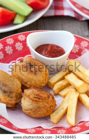 Minced meat in batter and fried potatoes with sauce on a plate