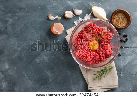 Minced meat in bowl with spices and egg, selective focus - stock photo