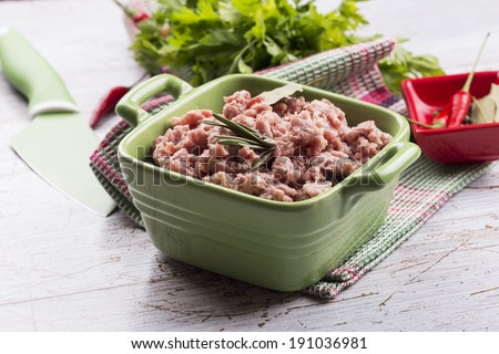 Minced meat in green bowl on white table with seasoning. Selective focus, horizontal.  - stock photo