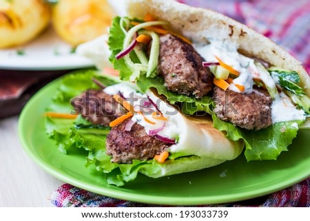 Minced meat kebab, beef balls in flat cake with vegetable, white sauce, spring picnic, Greek gyros