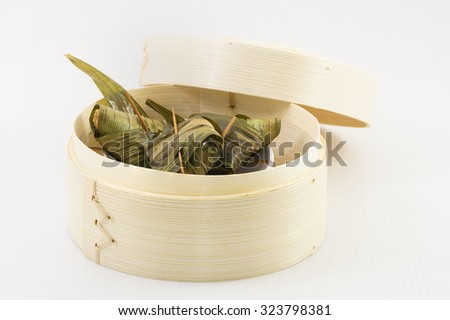 Minced meat mix with fish paste wrap with pandan leaf. A dim sum style Chinese cuisine prepared as small bite-size portion of food traditionally served in small steamer basket or on small plate. - stock photo