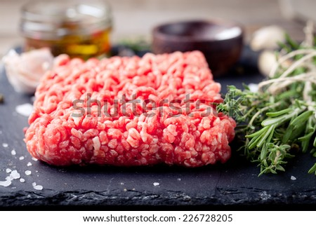 Minced meat on a slate stone black board with fresh herbs. - stock photo