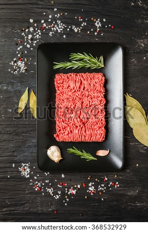 Minced meat on black plate with seasoning and fresh rosemary on black background, top view - stock photo