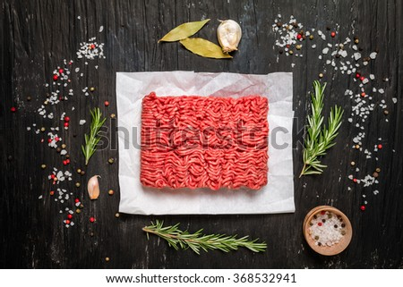 Minced meat on paper with seasoning and fresh rosemary on black background, top view - stock photo