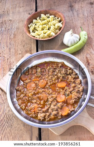 Minced meat sauce with vegetables cooked in pan with pasta - stock photo