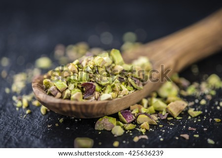 Minced Pistachios (detailed close-up shot; selective focus) on vintage background