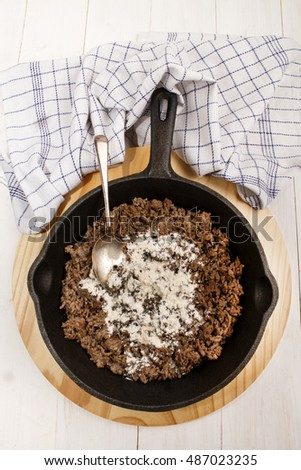 minced pork meat with flour to prepare a sauce in a cast iron pan