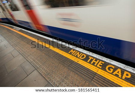 Mind the gap sign with speeding train in London underground. - stock photo