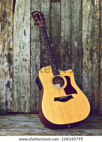 MINDEMOYA, ONTARIO, CANADA-July 3, 2011: Photograph of a Taylor acoustic guitar leaning against a rustic wooden wall. - stock photo