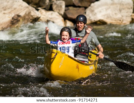 MINDEN, ONTARIO - SEPTEMBER 10: An unidentified contestant and his child compete at 2011 Open Canoe Slalom Race at Gull River in Minden, Ontario, Canada on September 10, 2011.