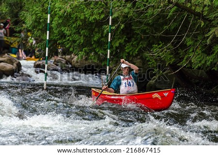 MINDEN, ONTARIO - SEPTEMBER 6, 2014: An unidentified contestant competes at 2014 Open Canoe Slalom Race at Gull River in Minden, Ontario, Canada.  - stock photo