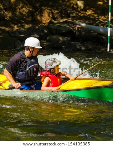 MINDEN, ONTARIO - SEPTEMBER 8: Father and son paddling a green canoe in Open Canoe Whitewater Race at Minden Whitewater Preserve on Gull River on September 8, 2013  - stock photo