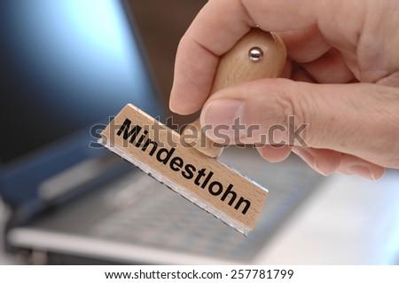 Mindestlohn printed on rubber rubber stamp in german language - minimum wage - stock photo