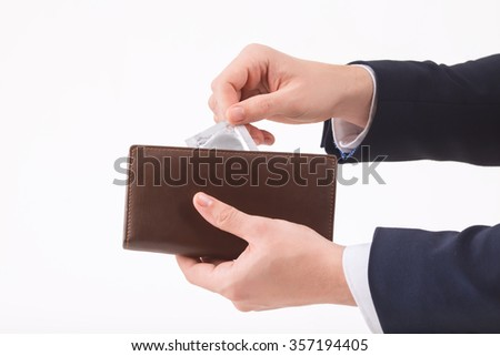Mindful person. Male hand putting a condom into the wallet.  - stock photo