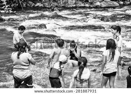 MINDO, ECUADOR - JAN 1, 2015: Unidentified tourists near and in the Mindo river. Mindo Valley is among the most popular touristic places in Ecuador.