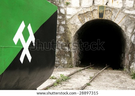 Mine shaft entrance and wagon with miners symbol - stock photo