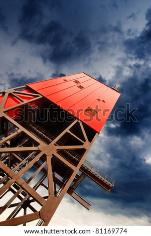 mine shaft tower on dramatic sky - stock photo