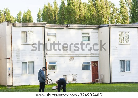 Minehead, Exmoor, England - May 23 2015 : Workers repairing an old table outside their living quarters at Butlins holiday camp.  - stock photo
