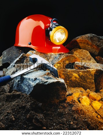 Miner's helmet with pick axe and rocks - stock photo