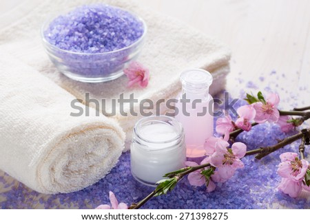 Mineral bath salts, towels and moisturizer  in a tranquil spa setting.   Shallow DOF. Focus on the  jar of cosmetic cream - stock photo