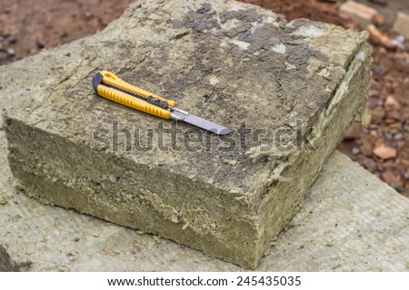 Mineral rockwool panel with a craft knive at construction site. Selective focus. - stock photo