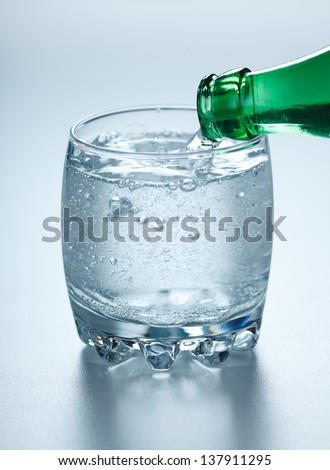 Mineral water being poured into glass from green bottle - stock photo