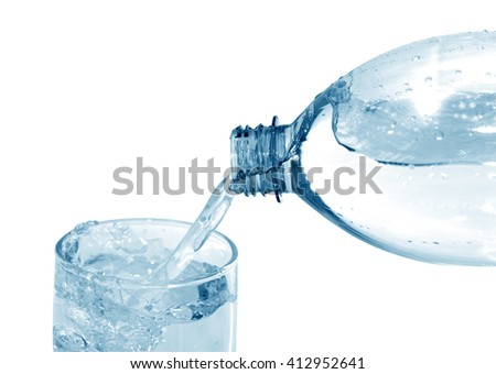 Mineral water flowing from bottle to glass. Isolated with clipping path
