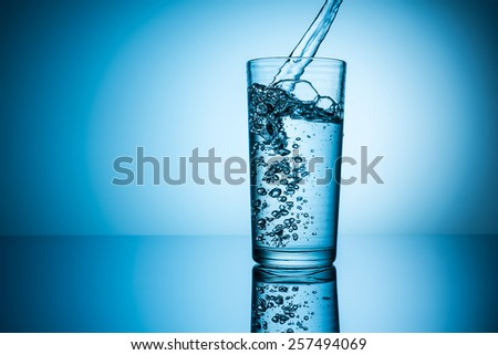 mineral water flows in to glass