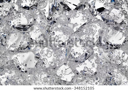 Mineral water forms gas bubbles between ice pieces of acrylic. - stock photo