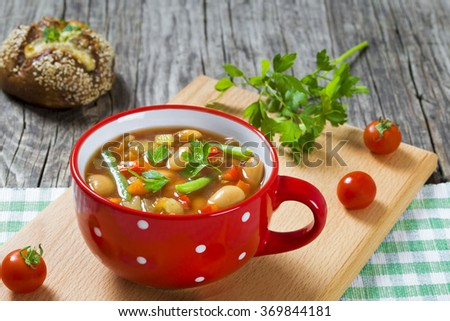 Minestrone vegan soup with bell pepper, beans, tomatoes in the soup cup  on the old rustic table with homemade rye bun, close-up, selective focus - stock photo