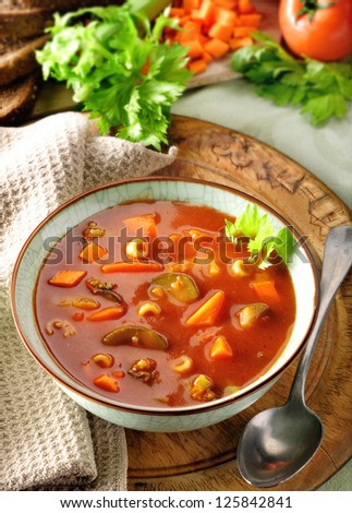 Minestrone, vegetable and tomato soup. Rustic setting with ingredients in the background. - stock photo