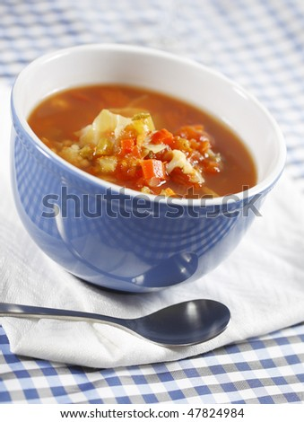 minestrone vegetable soup on a white napkin. Country style with blue checked nap and shallow depth of field. - stock photo