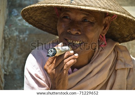 MINGUN, MYANMAR - AUGUST 17: unidentified nun smoking a big cheroot in Mingun, near Mandalay, August 17, 2007. A cheroot is a cigar made principally by dried fruits and little bit of tobacco - stock photo